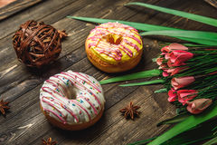 Multi-colored assortment of donuts. With sprinkles and frosting on dark wooden background with flowers Stock Photo
