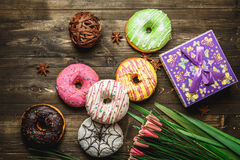 Multi-colored assortment of donuts. With sprinkles and frosting on dark wooden background with flowers Royalty Free Stock Photo
