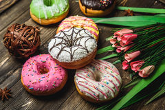Multi-colored assortment of donuts. With sprinkles and frosting on dark wooden background with flowers Royalty Free Stock Images