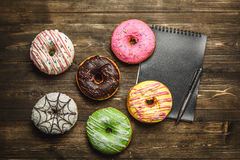 Multi-colored assortment of donuts. With sprinkles and frosting on dark wooden background. with a notebook and pen Royalty Free Stock Photos