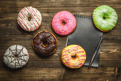 Multi-colored assortment of donuts. With sprinkles and frosting on dark wooden background. with a notebook and pen Stock Photo