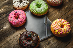 Multi-colored assortment of donuts. With sprinkles and frosting on dark wooden background. with a notebook and pen Royalty Free Stock Images