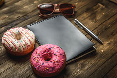 Multi-colored assortment of donuts. With sprinkles and frosting on dark wooden background. with a notebook and pen and sunglasses Royalty Free Stock Photos