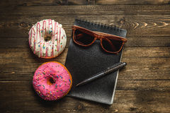 Multi-colored assortment of donuts. With sprinkles and frosting on dark wooden background. with a notebook and pen and sunglasses Stock Photo