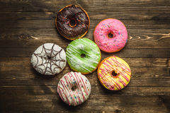 Multi-colored assortment of donuts. With sprinkles and frosting on dark wooden background. six sweet rings Stock Photography