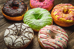 Multi-colored assortment of donuts. With sprinkles and frosting on dark wooden background. six sweet rings Stock Image