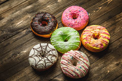 Multi-colored assortment of donuts. With sprinkles and frosting on dark wooden background. six sweet rings Royalty Free Stock Photography