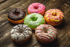 Multi-colored assortment of donuts. With sprinkles and frosting on dark wooden background. six sweet rings Royalty Free Stock Photo