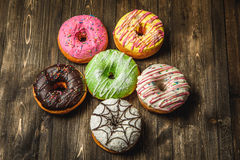 Multi-colored assortment of donuts. With sprinkles and frosting on dark wooden background. six sweet rings Royalty Free Stock Image