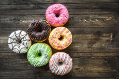 Multi-colored assortment of donuts. With sprinkles and frosting on dark wooden background. six sweet rings Royalty Free Stock Photos