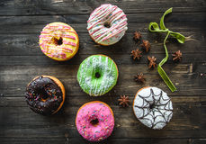Multi-colored assortment of donuts. With sprinkles and frosting on dark wooden background. six sweet rings Stock Photos