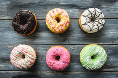 Multi-colored assortment of donuts. With sprinkles and frosting on light wooden background. six sweet rings Royalty Free Stock Photography