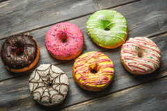 Multi-colored assortment of donuts. With sprinkles and frosting on light wooden background. six sweet rings Royalty Free Stock Photo