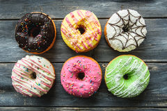 Multi-colored assortment of donuts. With sprinkles and frosting on light wooden background. six sweet rings Royalty Free Stock Photos