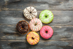 Multi-colored assortment of donuts. With sprinkles and frosting on light wooden background. six sweet rings Stock Photos