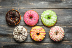 Multi-colored assortment of donuts. With sprinkles and frosting on light wooden background. six sweet rings Stock Images