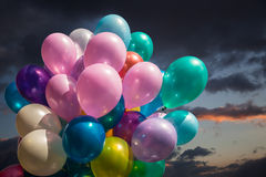 Multi-colored balloons against cloudy sky Royalty Free Stock Photography