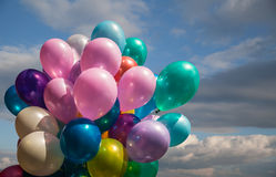 Multi-colored balloons against cloudy sky Royalty Free Stock Photo