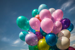 Multi-colored balloons on blue sky background Stock Photos