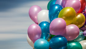 Multi-colored balloons on blue sky background Stock Images