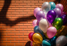 Multi-colored balloons on brick wall background Royalty Free Stock Photo