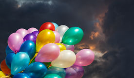 Multi-colored balloons on dark dramatic sky Stock Photo
