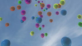 Multi-colored balloons floating in a blue sky stock video
