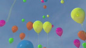 Multi-colored balloons floating in a blue sky stock footage