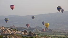 Multi-colored balloons fly over rocks stock video