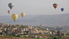 Multi-colored balloons fly over rocks. stock video