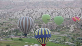 Multi-colored balloons fly over rocks stock video footage
