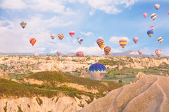 Multi-colored balloons fly over rocks. Royalty Free Stock Photos