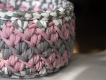 Crocheted basket crochet from knitting yarn. Multi-colored basket with loop, crocheted thick knitted yarn. Pink, white, grey, melange Stock Images