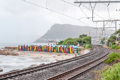 Multi-colored beach huts at St. James with railroad passing by Royalty Free Stock Images