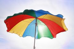 Multi-colored beach umbrella against the background of a light s. Ky. For summer season Stock Photography