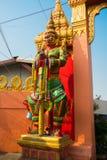 Multi-colored beeldhouwwerk van een strijder met een zwaard met een rood gezicht bij een Boeddhistische tempel Nakhon Ratchasima  Stock Foto's
