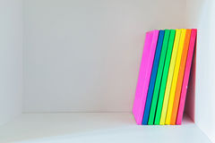Multi colored books on the light-coloured bookshelf Stock Photography