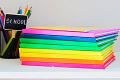 Multi colored books in stack on the light-coloured bookshelf Royalty Free Stock Images