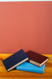 Multi-colored books on wooden table. Back to school. Copy space for text. Education business concept. Multi-colored books on a wooden table and red background royalty free stock images