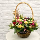 Multi-colored bouquet of flowers in basket stock photography