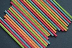 Multi-colored bright Indian incense sticks lie parallel on a dark gray background, top view royalty free stock photography