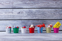 Multi-colored bucket with gifts on wooden background. Royalty Free Stock Images