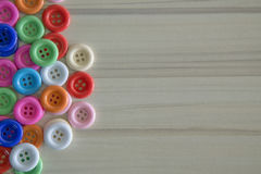 A Multi colored buttons on light wood table Royalty Free Stock Image