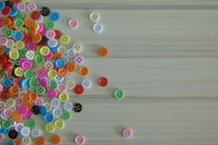 A Multi colored buttons on light wood table Stock Photography