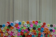 A Multi colored buttons on light wood table Royalty Free Stock Photo