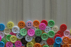 A Multi colored buttons on light wood table Stock Image