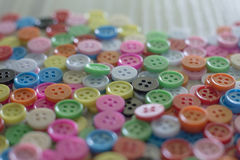 A Multi colored buttons on light wood table Royalty Free Stock Images
