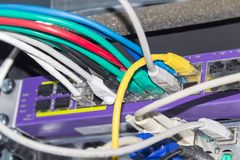 Multi-colored cables connected to equipment in telecommunication. Fragment of a rear part of the telecommunication rack with equipment and connected different Stock Photography