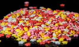 Multi-colored candies in the form of stars on a black royalty free stock photo