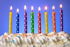 Multi-colored candles burn on a birthday cake on blue background